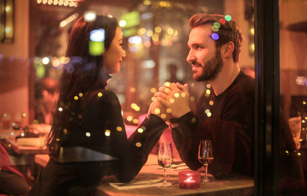 Couple holding hands at a restaurant table